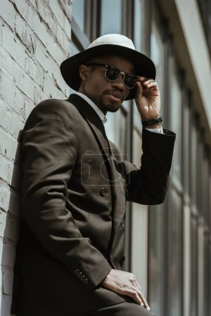 Fashionable african american businessman wearing fedora hat and sunglasses posing by building wall