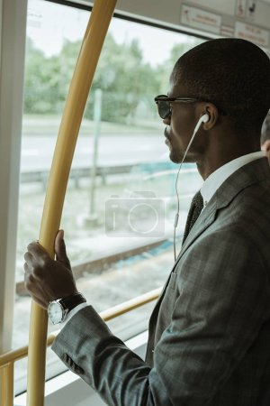 African american confident businessman listening to music while going to work by train