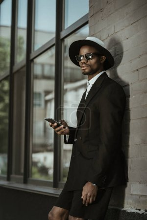 Fashionable african american man wearing fedora hat and using smartphone in city