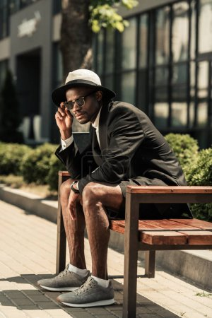 Fashionable african american man wearing fedora hat sitting on bench