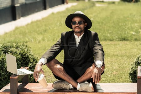 Handsome young african american man sitting on bench by laptop