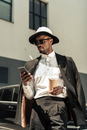 Photo for Handsome young african american businessman listening to music and holding coffee cup - Royalty Free Image