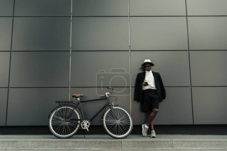 Photo for Fashionable african american man wearing fedora hat using smartphone while standing by his bicycle - Royalty Free Image