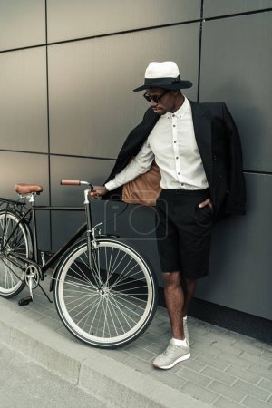 Photo for Stylish man wearing white shirt and jacket standing by his bicycle - Royalty Free Image