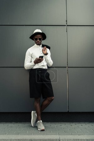 Handsome young african american man using smartphone while standing by building wall