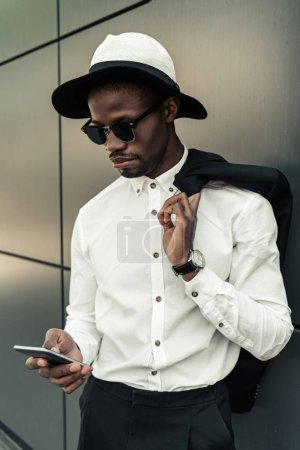Fashionable african american businessman wearing fedora hat and using smartphone