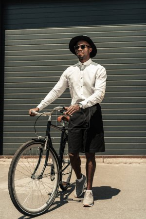 Handsome young african american man holding bike