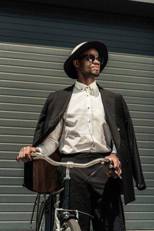 Fashionable african american man wearing fedora hat holding bike