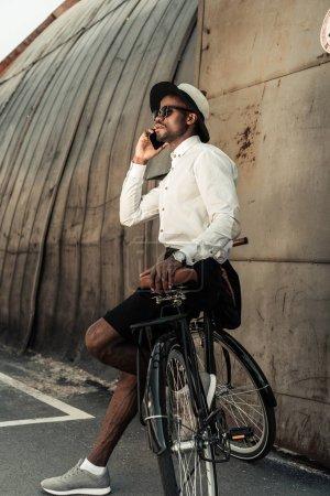 Stylish man wearing white shirt leaning on bike and talking on smartphone