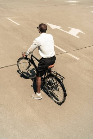 Photo for Fashionable african american man riding bike on street - Royalty Free Image