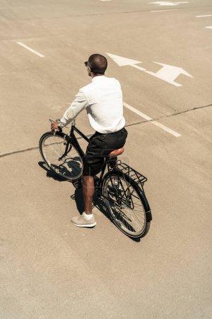 Fashionable african american man riding bike on street