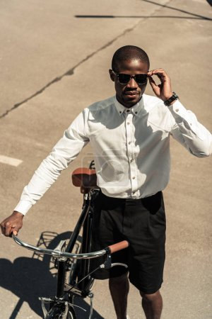 Fashionable african american man standing by his bicycle on street