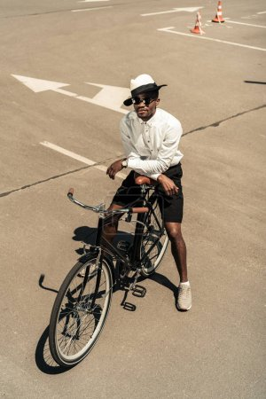 Fashionable african american man wearing fedora hat and sunglasses posing by city bike