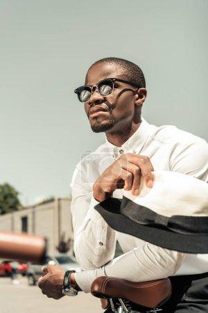 Photo pour Beau jeune homme afro-américain dans lunettes de soleil se penchant sur le vélo de ville - image libre de droit