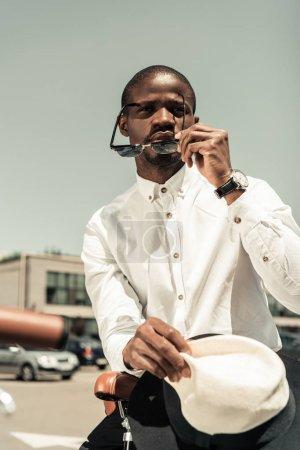 Stylish man wearing white shirt and sunglasses leaning on city bike