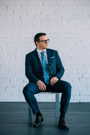 serious middle aged businessman in suit and eyeglasses sitting on chair and looking away