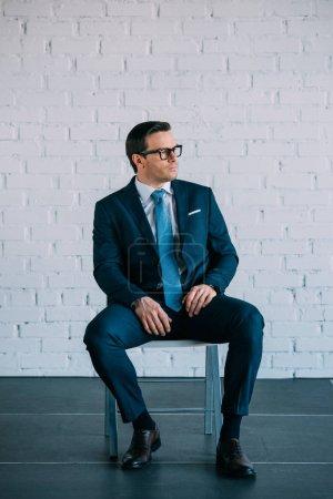 homme d'affaires âgé moyen sérieux en costume et lunettes assis sur la chaise et à la recherche de suite