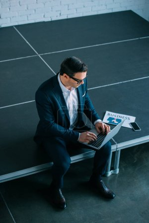 high angle view of middle aged businessman sitting and using laptop