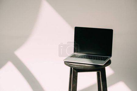 open laptop with black screen on stool on grey