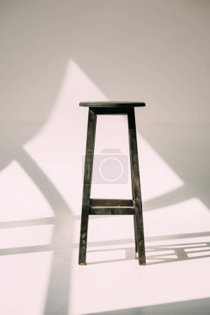 single empty tall wooden stool on white