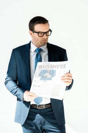 serious middle aged buisnessman in eyeglasses reading newspaper isolated on white