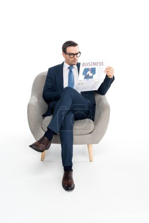 full length view of serious businessman in eyeglasses reading newspaper while sitting in armchair isolated on white