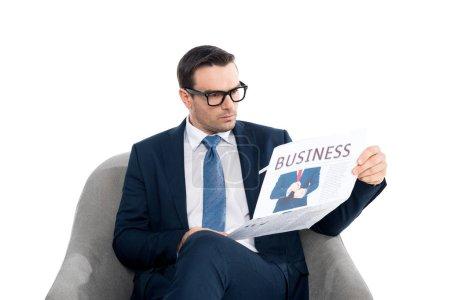 Photo pour Homme d'affaires sérieux en lisant le journal tout en étant assis dans le fauteuil isolé sur blanc de lunettes de vue - image libre de droit