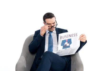 focused businessman adjusting eyeglasses and reading newspaper while sitting in armchair isolated on white