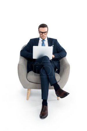 full length view of handsome businessman in eyeglasses sitting in armchair and using laptop on white