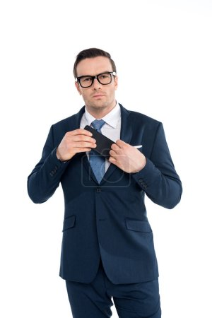 handsome businessman in eyeglasses looking at camera while holding smartphone isolated on white