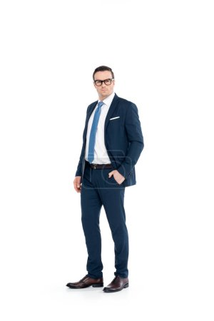 full length view of confident businessman in eyeglasses and suit standing with hand in pocket and looking at camera isolated on white