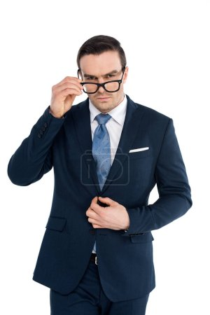 Photo for Handsome businessman adjusting eyeglasses and looking at camera isolated on white - Royalty Free Image