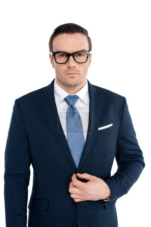 handsome buisnessman in eyeglasses and suit looking at camera isolated on white