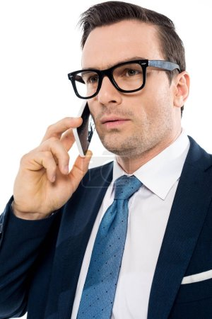 Photo for Handsome businessman in eyeglasses talking by smartphone and looking away isolated on white - Royalty Free Image
