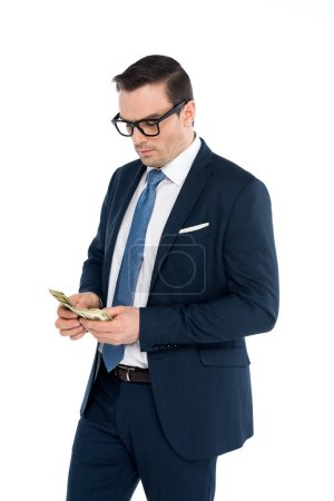 handsome businessman in eyeglasses counting dollar banknotes isolated on white