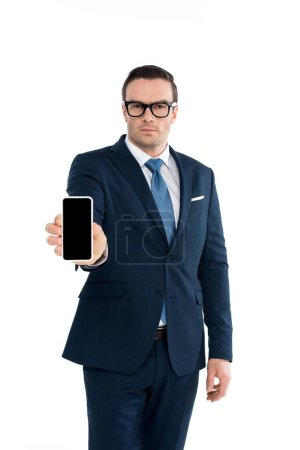 Photo for Handsme businessman in eyeglasses holding smartphone with blank screen and looking at camera isolated on white - Royalty Free Image