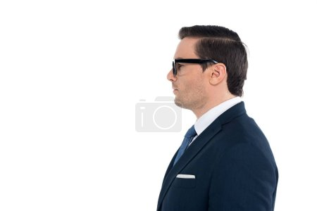 side view of businessman in suit and eyeglasses standing and looking away isolated on white