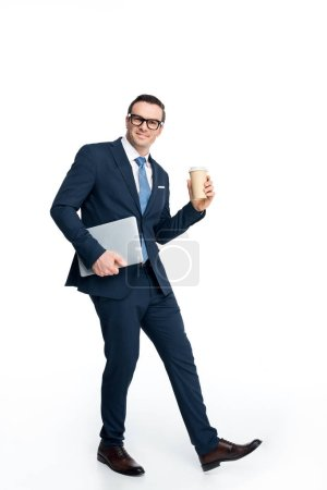 Photo for Full length view of handsome businessman holding laptop and paper cup and smiling at camera isolated on white - Royalty Free Image