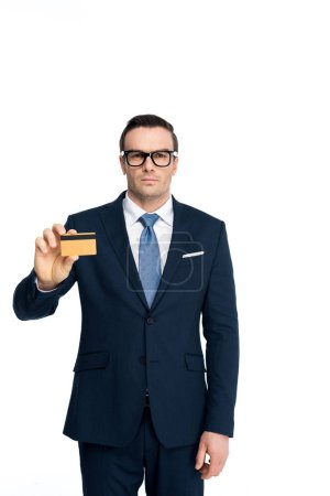Photo for Handsome businessman in eyeglasses holding credit card and looking at camera isolated on white - Royalty Free Image
