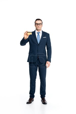 full length view of serious businessman in suit and eyeglasses holding credit card and looking at camera isolated on white