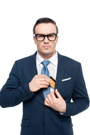 businessman in eyeglasses putting credit card in suit jacket pocket and looking at camera isolated on white