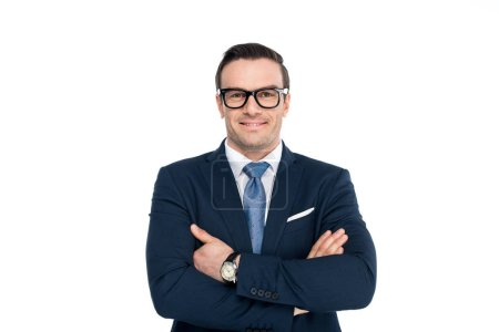 confident businessman in eyeglasses standing with crossed arms and smiling at camera isolated on white