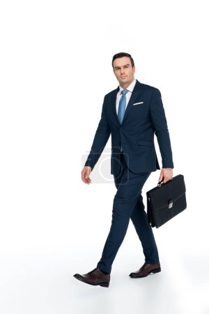 Photo for Full length view of businessman with briefcase walking and looking at camera on white - Royalty Free Image