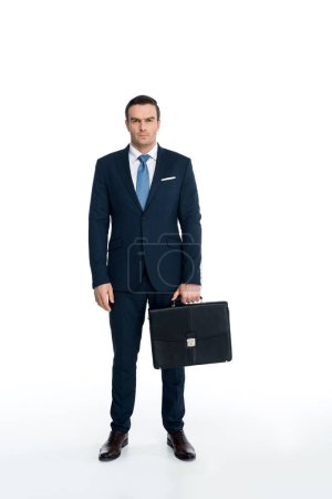 Photo for Full length view of serious middle aged businessman holding briefcase and looking at camera on white - Royalty Free Image