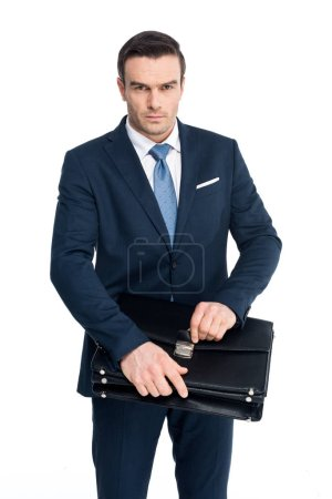 serious middle aged businessman holding briefcase and looking at camera isolated on white