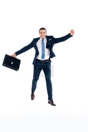 excited businessman with briefcase jumping and smiling at camera isolated on white