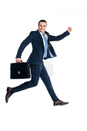 businessman with briefcase jumping and smiling at camera isolated on white
