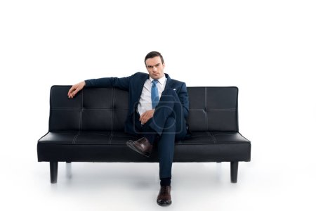 confident middle aged businessman sitting on couch and looking at camera on white
