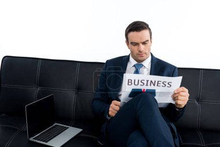 middle aged businessman reading newspaper while sitting on couch with laptop isolated on white