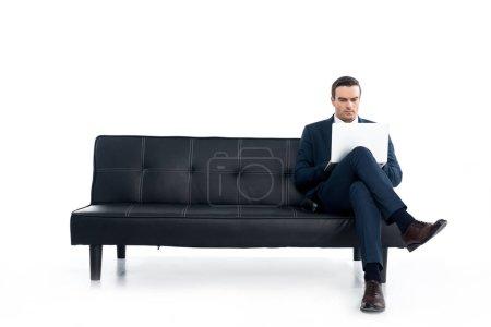 środkowy biznesmen wieku siedzi na kanapie i komputera przenośnego na białym